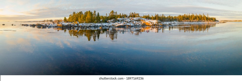 Panoramic view of Scenic Winter Sunset Reflections From Iced Sea to small stony peninsula Kont, Umea, Sweden. Winter scandinavian pine tree forest at sea coastline