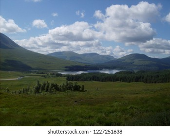 Panoramic view of the Scottish Highlands with a beautiful lake that is reflecting the fluffy white clouds in the sky surrounded by a lush green forest and meadow. Scotland, United Kingdom