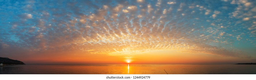 Panoramic view of the sea or ocean with a stunning sunset and feather clouds that stretch across the horizon.