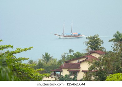 Panoramic view of the sea, a scuna sailing and the houses in Ilhabela, Brazil.