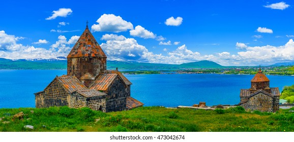 Panoramic view of Sevan Peninsula with both Churches of Sevanavank Monastery - Holy Apostles and Holy Mother of God, on the green meadow and with the pure Sevan Lake on the background, Armenia.