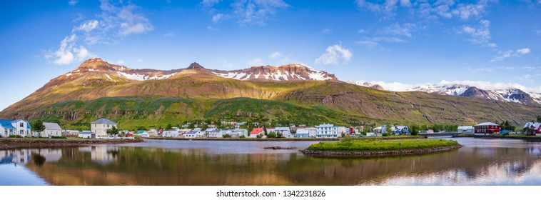 Panoramic view of Seydisfjordur with houses and surrounding landscape reflecting in Fjardara lake. Seydisfjordur is a small picturesque town and port at Seydisfjordur fjord in Eastern Iceland