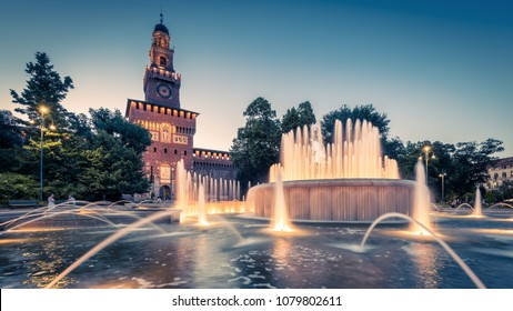Panoramic view of Sforza Castle (Castello Sforzesco) with lighting fountain at night, Milan, Italy. This castle was built in the 15th cent by Sforza, Duke of Milan and is a famous landmark of Milan.