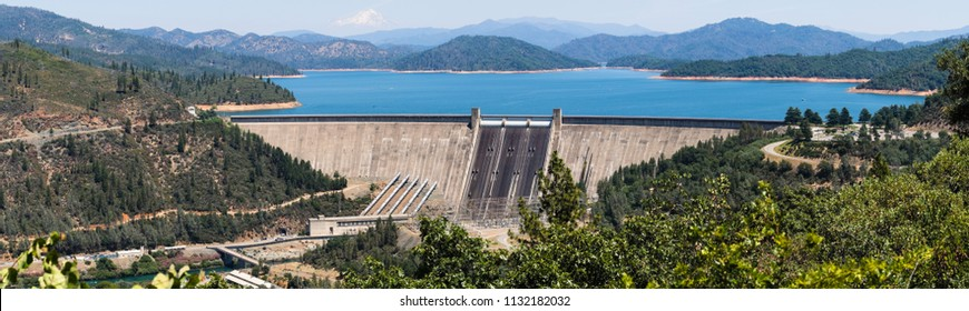 Panoramic view of Shasta Dam on a sunny day, Shasta mountain visible in the background; Northern California