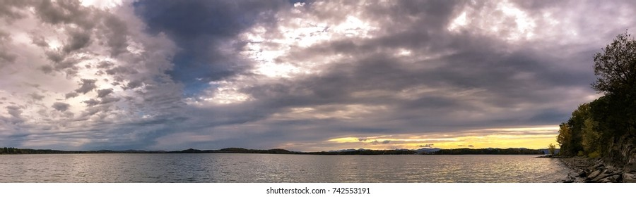 Panoramic view of Shelburne Bay Lake Champlain in Vermont during fall time an hour before sunset.  Autumn colors are vivid yellow and red