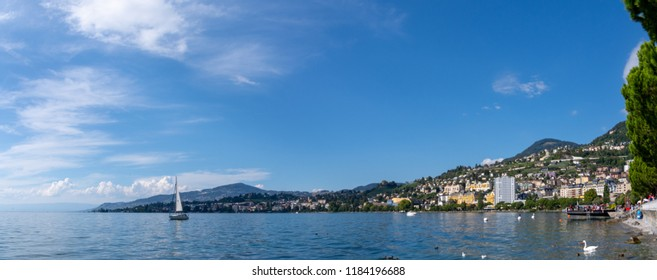 Panoramic view of the shoreline of clarens and montreux at lac leman / lake geneva as seen from the Montreux, Switzerland with wonderful weather and a beautiful blue cloudy sky