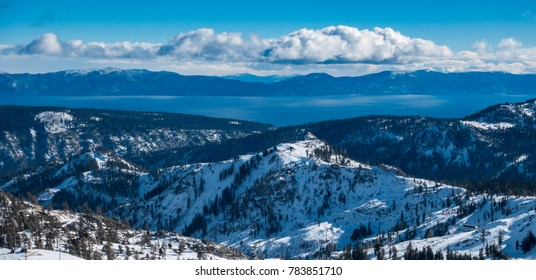 Panoramic view of the Sierra Nevada Mountains, with Lake Tahoe in the background, from the top of the Squaw Valley Ski Resort, between Truckee and Tahoe City, on a partly cloudy winter day in December
