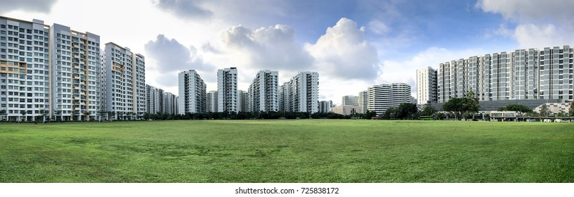 Panoramic view of Singapore Public Housing Apartments in Punggol District, Singapore. Housing and Development Board(HDB) on green grass field with cloudy sky