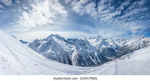 Panoramic view of the ski slope with the mountains Belalakaya, Sofrudzhu, Sulakhat and Semenov-Bashi on the horizon in winter day. Dombai ski resort, Western Caucasus, Karachai-Cherkess, Russia.