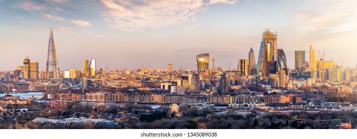 Panoramic view to the skyline of London, UK, during a golden sunrise: from the City to the Tower Bridge