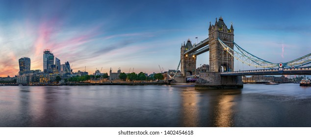 Panoramic view of the skyline of London, UK, during evening: from the Tower Bridge along the Thames river to the skyscrapers of the City
