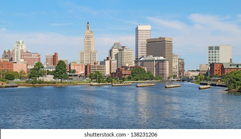 Panoramic view of the skyline of Providence, Rhode Island, from the far side of the Providence River against a blue sky and white clouds