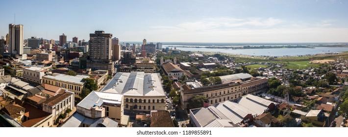 Panoramic view of skyscrapers skyline of Latin American capital of Asuncion city, Paraguay. Embankment of Paraguay river. Birds eye aerial drone photo. Ciudad de Asunción Paraguay. South America.