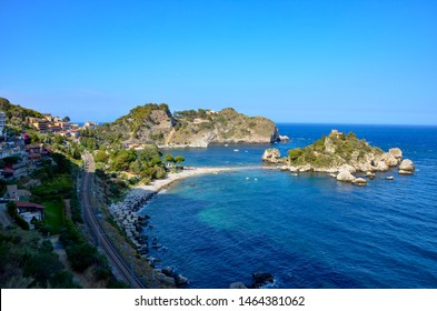 Panoramic view to the small island called Isola Bella in the Ionian sea offshore the coast of Taormina in Sicily, traditional houses on the left, railway tracks nearby, movie location of godfather