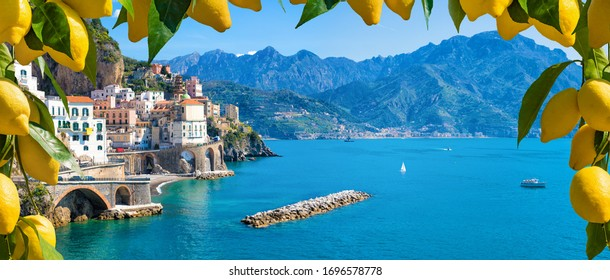 Panoramic view of small town Atrani on Amalfi Coast in province of Salerno, Campania region, Italy. Amalfi coast is popular travel and holyday destination in Italy. Ripe yellow lemons in foreground. - Shutterstock ID 1696578778