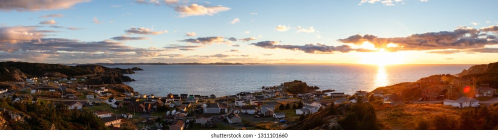 Panoramic view of a small town on the Atlantic Ocean Coast during a vibrant sunset. Taken in Crow Head, North Twillingate Island, Newfoundland and Labrador, Canada.