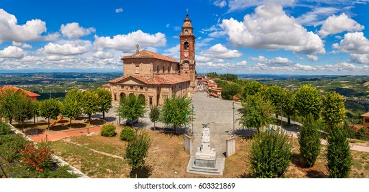 Panoramic view of small town square and parish church under beautiful sky in Diano d'Alba, Piedmont, Northern Italy.