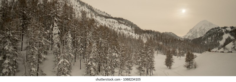 Panoramic view of snow capped mountain valley on overcast day. Sun behind clouds low on the horizon. Pine trees on the ridge of the mountain. Vintage, retro look. Pastel tone.
