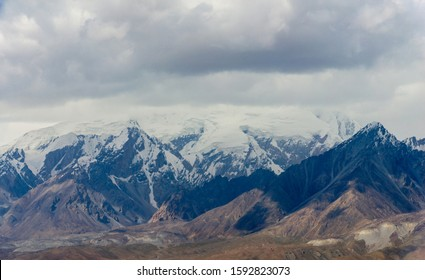 Panoramic view of snow capped mountain ranges and cloudscape of Kunlun mountians in Pamirs plateau in Xinjiang of China