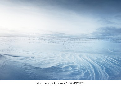 Panoramic view of the snow-covered field after a blizzard at sunset. Human tracks in a fresh snow. Ice desert. Dramatic cloudscape. Global warming theme. Lapland, Finland