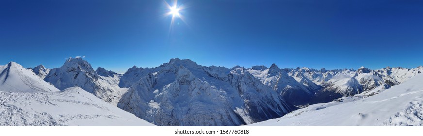Panoramic view of snowy mountains peaks in the clouds blue sky Caucasus