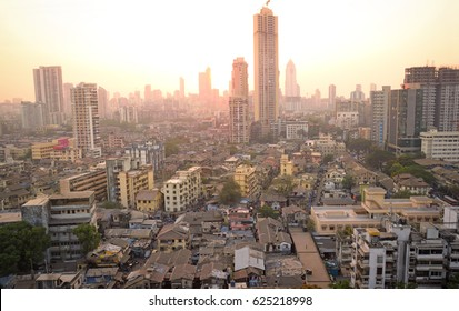 Panoramic view of south central Mumbai at dusk showing vast contrast in living conditions of people with dwellings of lower middle class in foreground and towers where elite stay in the far background
