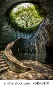 Panoramic view of a spiral staircase of an underground crossing in tunnel at Fort Canning Park, Singapore