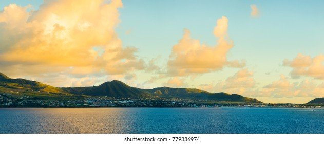Panoramic view of St Kitts from the sea during golden hour at dawn.
