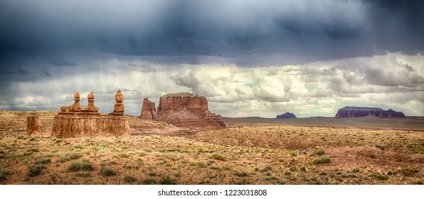 Panoramic view of stunning Hoodoos sandstone formations in famous Goblin Valley State Park on a beautiful sunny day with dark clouds and thunderstorm in summer, Utah, USA