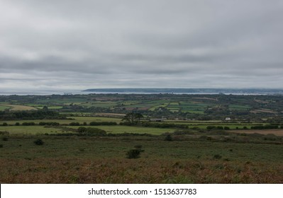 Panoramic View from the Summit of Godolphin Hill Looking Across Farmland with Mounts Bay, St Michael's Mount and Penzance in the Background in Rural Cornwall, England, UK