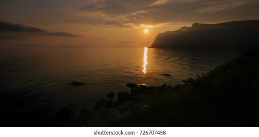 Panoramic view of the sun and the sunset over the sea. the mountains in the background