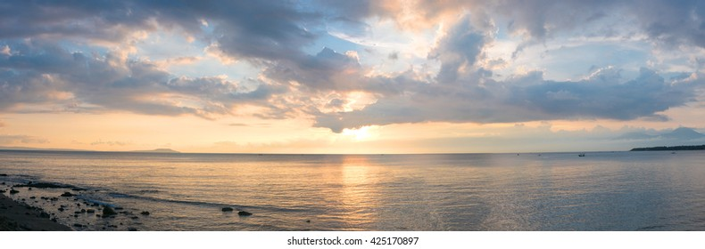 Panoramic view of sunset from Negara beach on Bali Island with Java volcano in the background. Indonesia