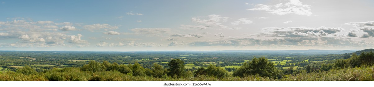 Panoramic view of the Surrey and Sussex countryside from the North Downs to the South Downs in England, UK. Taken from the Iron Age Hill Fort on top of Holmbury Hill on a cloudy summer's day.