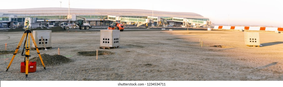 Panoramic view of surveyor equipment (theodolite or total positioning station) on the construction site of the building or airport