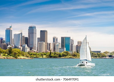 Panoramic view at Sydney city skyscrapers from ferry with blue sky and clouds on a bright day