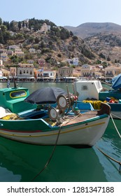 panoramic view of Symi with a fishing boat in the foreground and a hill with a monastery and a church in the background