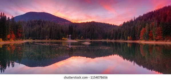 Panoramic view of Synevir high altitude lake at autumn sunset the leaf fall.