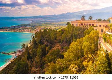 A panoramic view of Taormina, Giardini Naxos and Mount Etna, in Sicily, Italy. Photo taken from Via Teatro Greco, in Taormina.