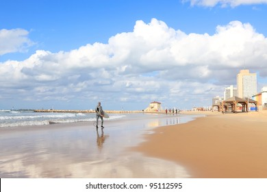 Panoramic view of Tel-Aviv beach and men going to surfing. Mediterranean sea. Israel