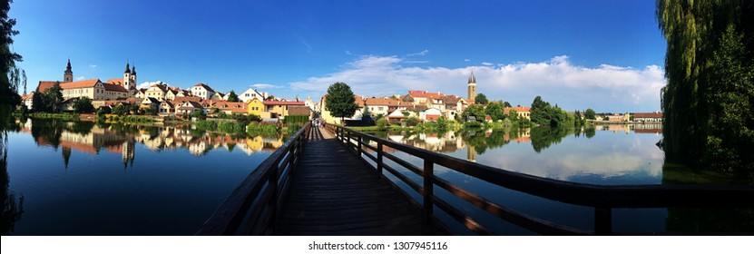 Panoramic view of Telc with blue sky and historical buildings reflection in the Ulicky pond and wooden bridge.