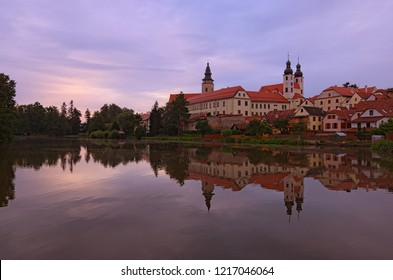 Panoramic view of Telc castle, pond with park, Name of Jesus Church and tower of the Church of St. Jakub. Buildings are reflected in the water. Early morning landscape. A UNESCO World Heritage Site.