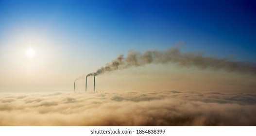 Panoramic view of thermoelectric power plant with dense smoke and colorful sky. Thermal chimneys producing smoke with toxic gases into atmosphere. Concept of energy generation, ecology and pollutions