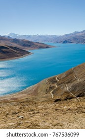 Panoramic view of Tibet natural landscape, blue azure water lake surrounded desert mountains. Yamdrok Lake (Yamdrok,  Yumtso, Yamzho, Yumco) is a one of the three largest sacred lakes in Tibet.