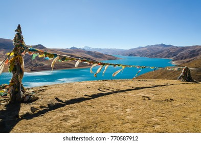 Panoramic view of Tibet natural landscape - blue azure water lake surrounded desert mountains. Yamdrok Lake (Yamdrok,  Yumtso, Yamzho, Yumco) is a sacred lake in Tibet.