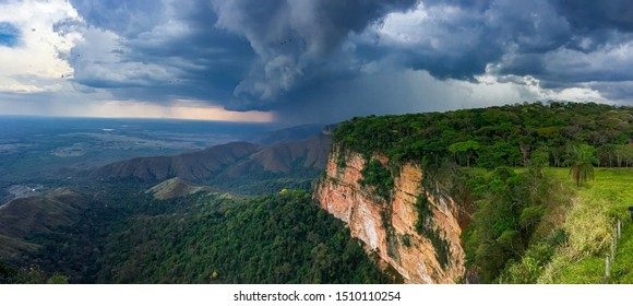 Panoramic view from top of cliffs with dark sunlight on cliffs and storm clouds and rain, Chapada dos Guimarães, Mato Grosso, Brazil, South America