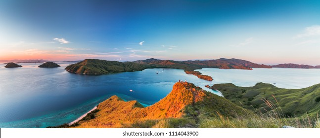 Panoramic view from top of Gili Lawa in morning when sunrise shining through the below hill with clear blue sea and tourist boats, Komodo Island (Komodo National Park), Labuan Bajo, Flores, Indonesia
