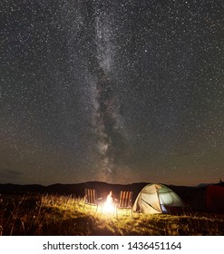 Panoramic view of tourist camping at night in the mountains. Glowing tent, two chairs and bonfire under amazing night sky full of stars and Milky way. Tourism active lifestyle astrophotography concept