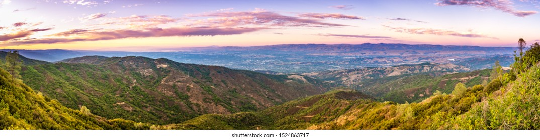 Panoramic view towards San Jose and south San Francisco bay at sunset; Hills and valleys in the Santa Cruz mountains in the foreground; Diablo Range visible on the other side of the valley, California