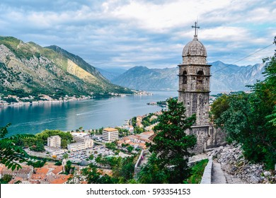 Panoramic view of town and mountains with church in foreground in Kotor, Montenegro