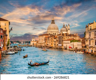 Panoramic view of traditional Gondola on famous Canal Grande with Basilica di Santa Maria della Salute in beautiful golden evening light at sunset in Venice, Italy